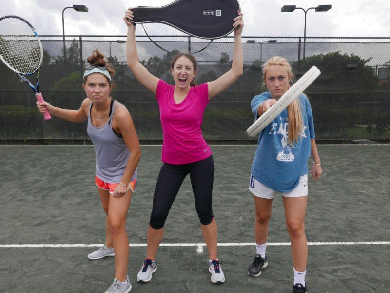 Três tenistas com raquetes fazendo pose para a câmera