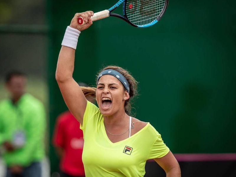 Carol Meligeni com raquete comemorando